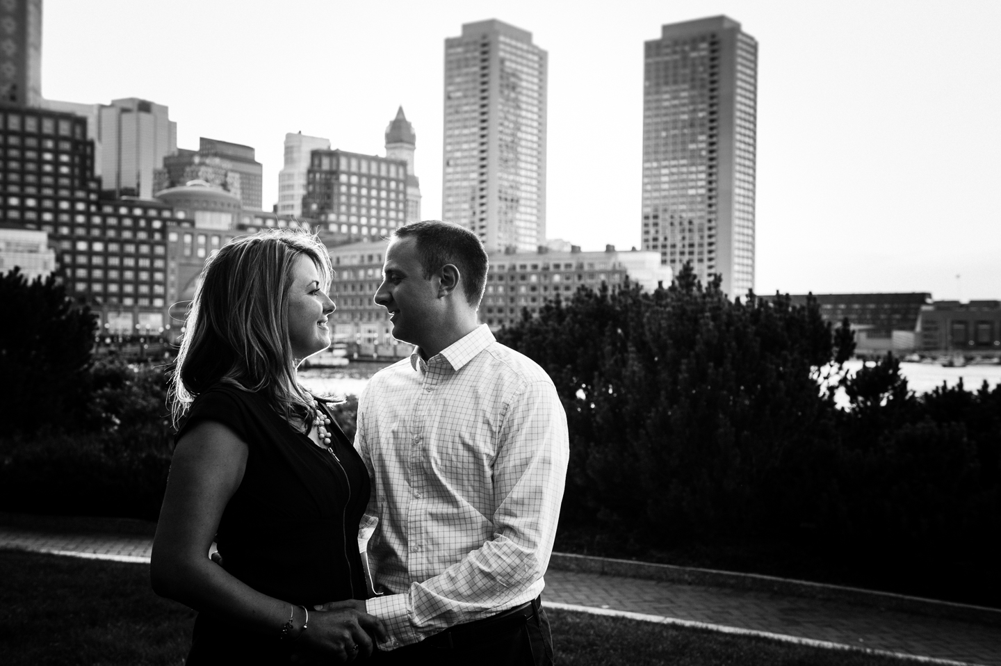 recently engaged couple poses facing each other with the boston city skyline behind