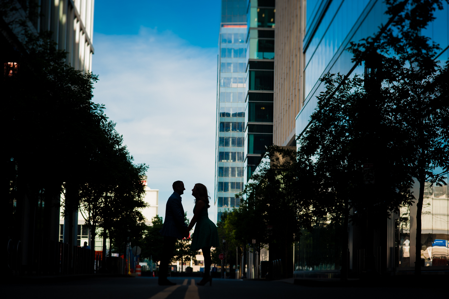 silhouette of couple against the blue sky and backlit buildings during their engagement session