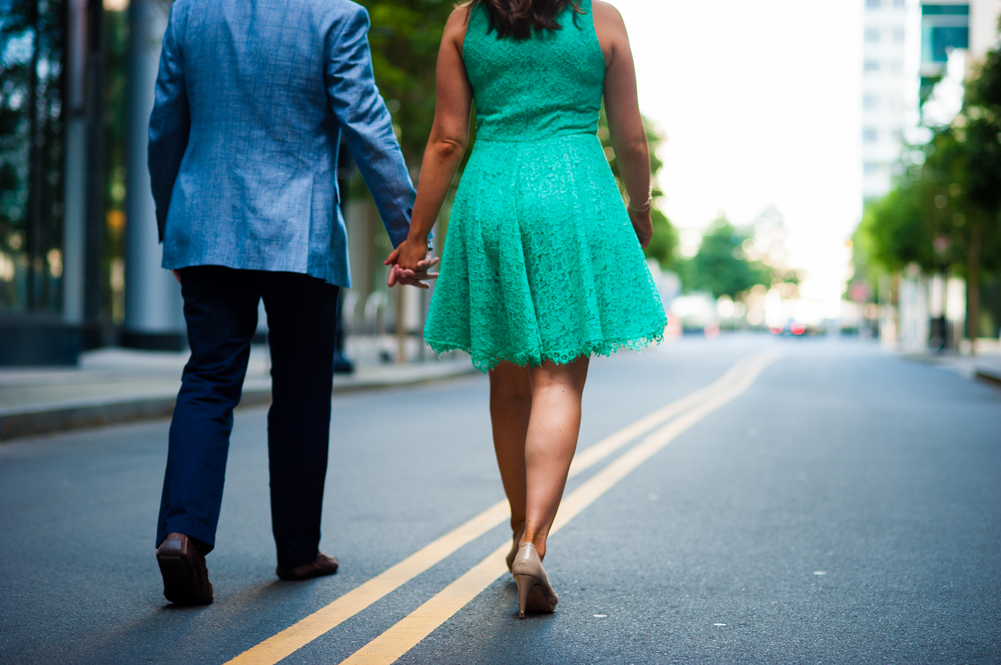 recently engaged couple holds hands and walks down the yellow line of a side street