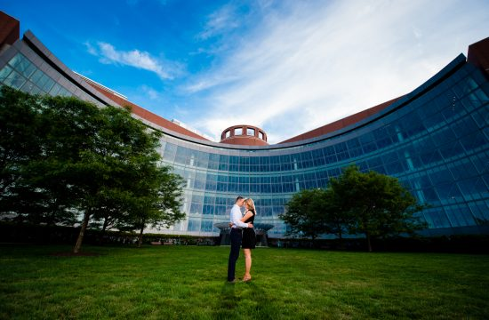 Couple embraces in front of gorgeous glass front building during their sunset engagement session
