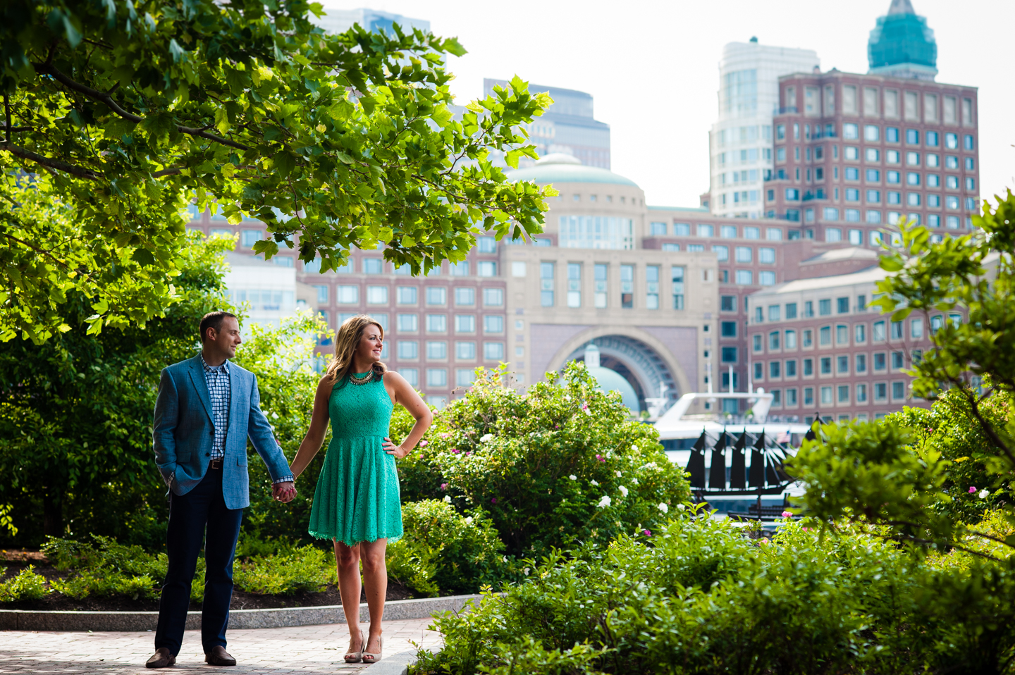 beautiful couple holds hands in front of boston skyline during their city engagement session