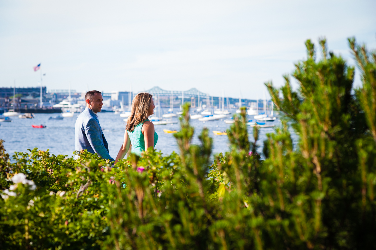 engaged  couples walks by the boston harbor waterfront during their sunset engagement session