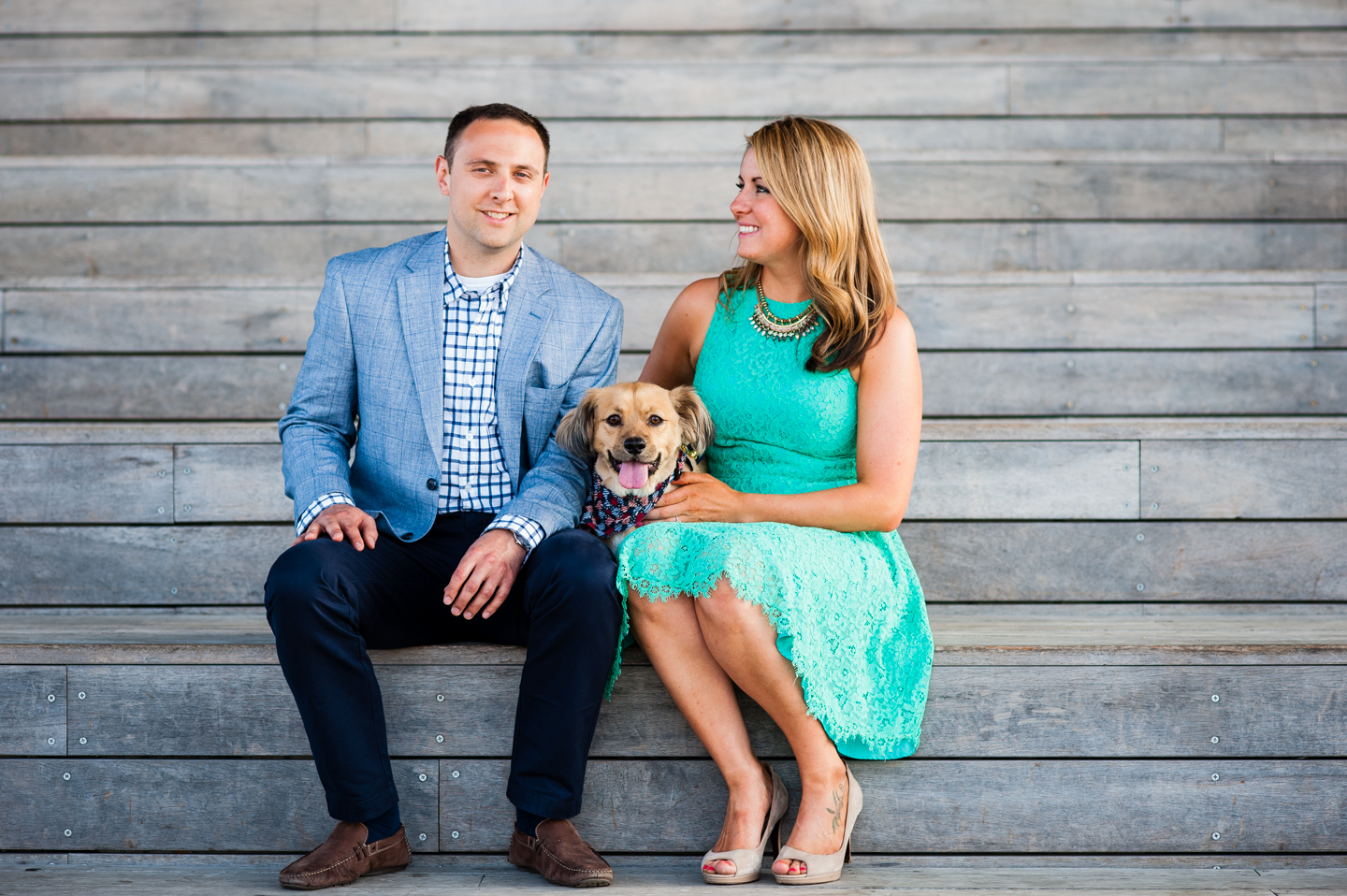 adorable engaged couple sits with their puppy on wooden stairs