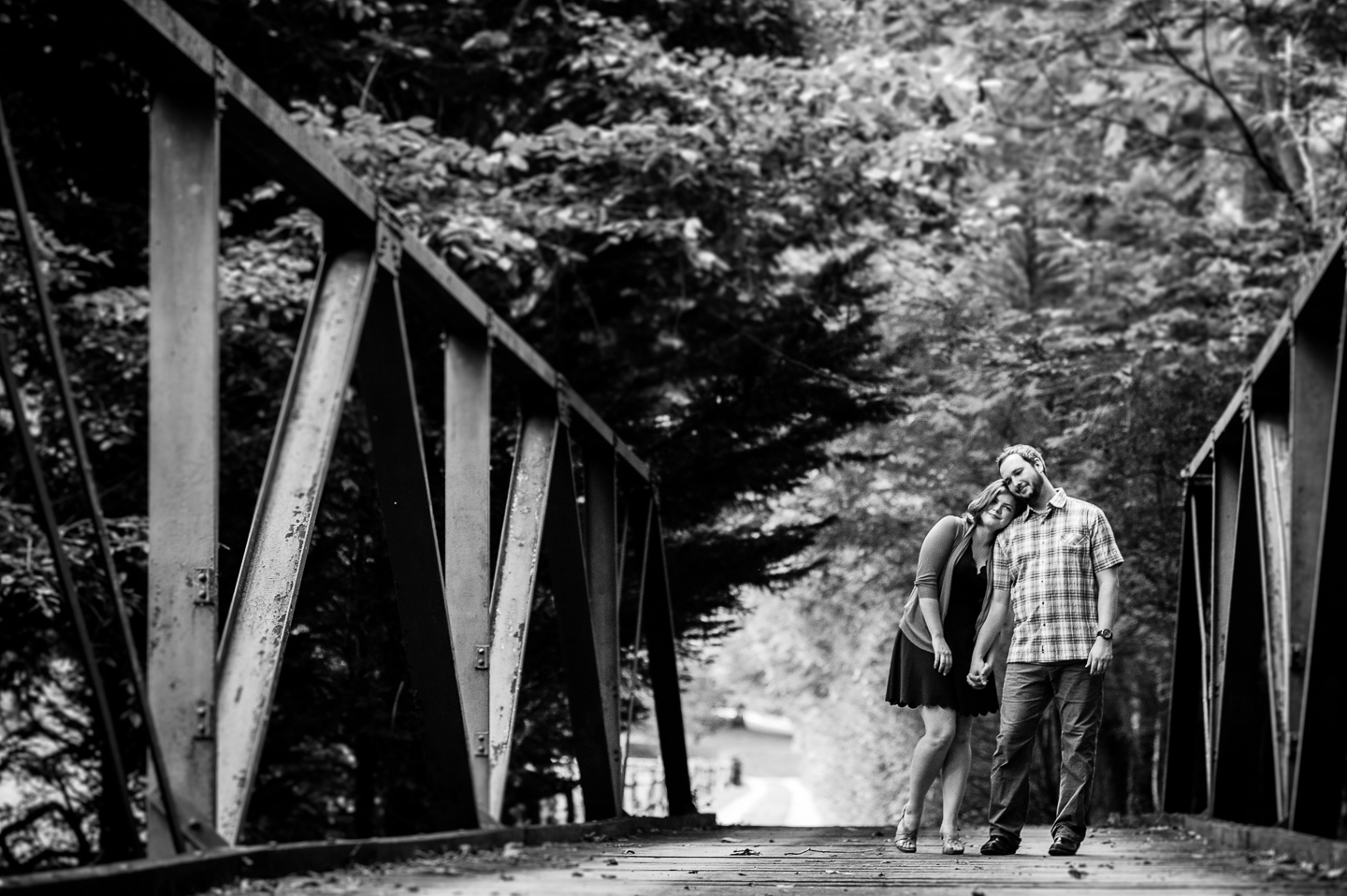 Gorgeous bride and groom pose on old wooden bridge during their wedding party outside Asheville NC