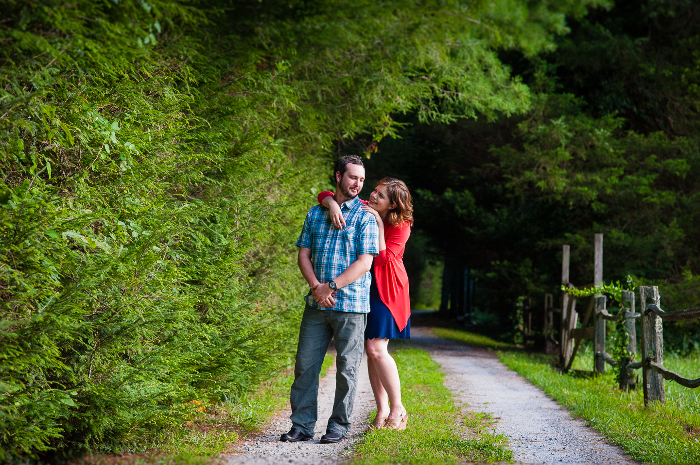 bride looks up at her groom as they pose along a wooded gravel driveway