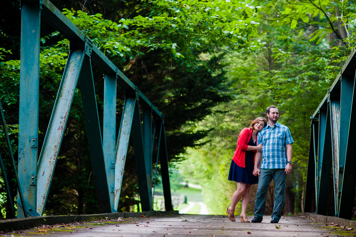 bride and groom pose for a picture on gorgeous wooden bridge in the forest during their backyard wedding