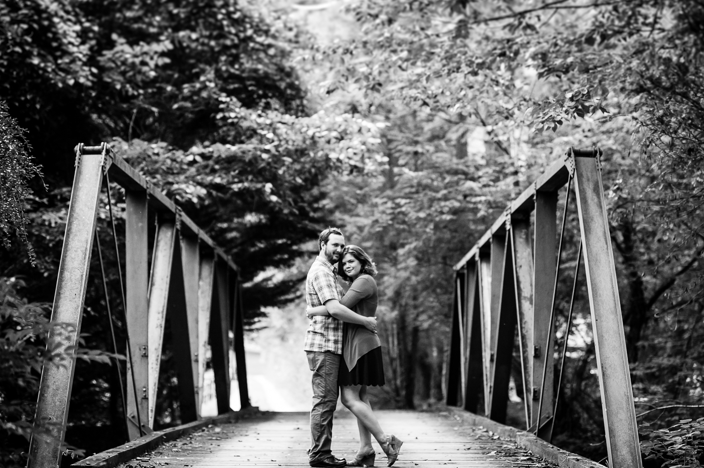 bride and groom embrace in the middle of old wooden forest bridge