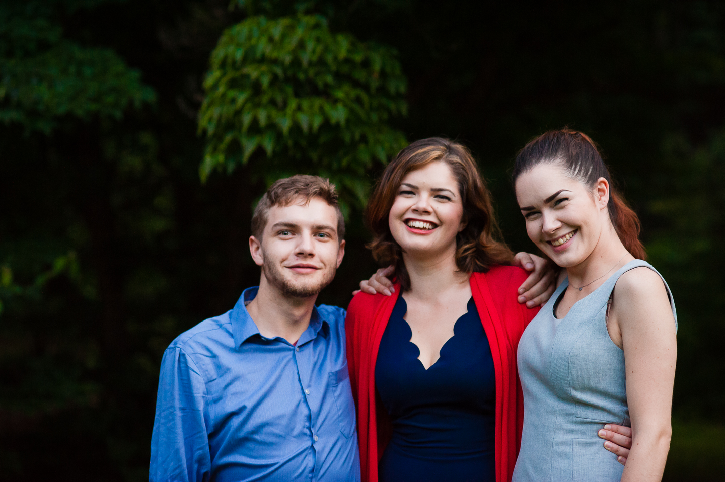 bride and her two siblings smile for a quick family picture