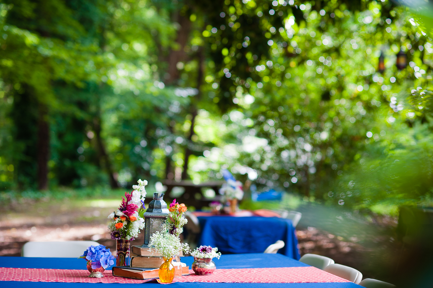 picnic tables with blue table clothes and handpicked flowers were the feature of this DIY backyard wedding