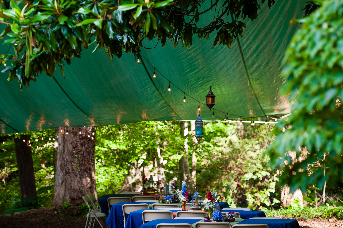 beautiful flowers adorned the bright blue table clothes which sat underneath hand strewn lanterns