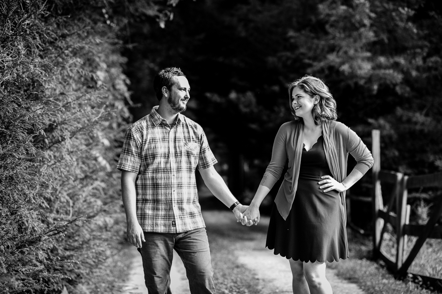 adorable bride and groom hold hands and steal glances at each other during their wedding portraits