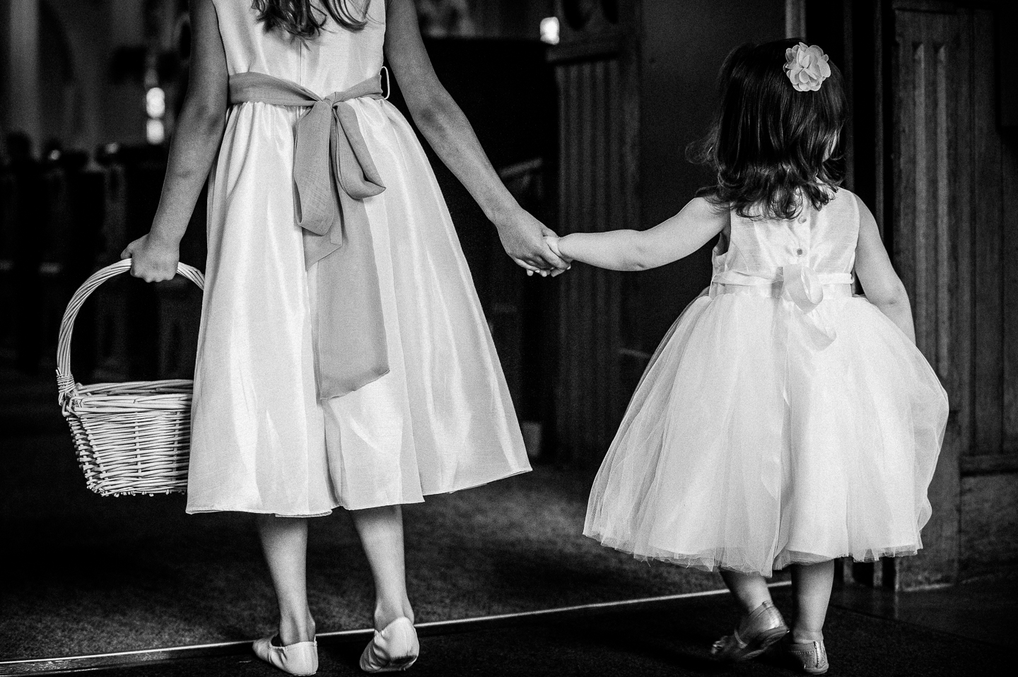two adorable flowers girls hold hands as they begin to walk down the aisle