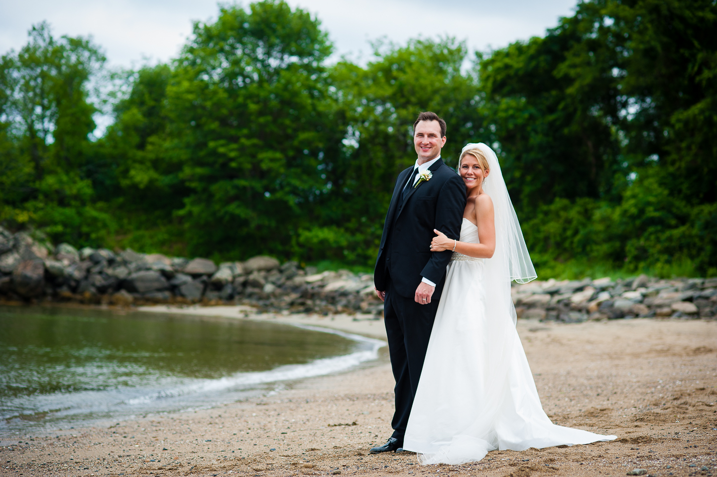 beautiful bride and groom pose on the beach during their seaside destination wedding
