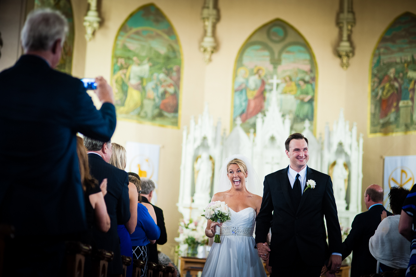 a very happy bride and groom walk down the aisle  as husband and wife