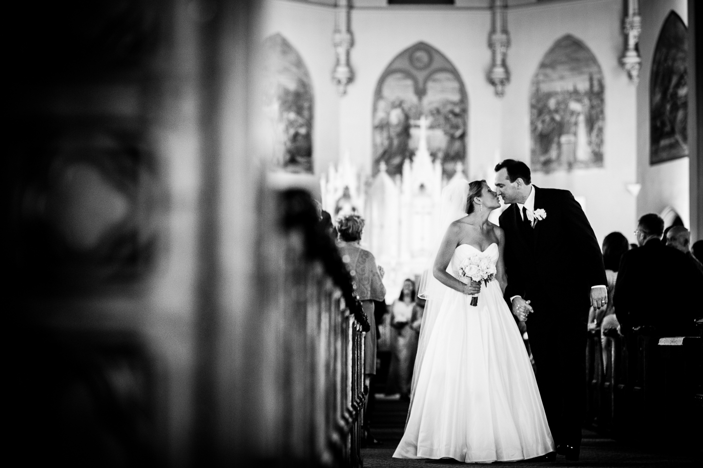 Newly married couple gives each other a kiss during their walk up the aisle as husband and wife