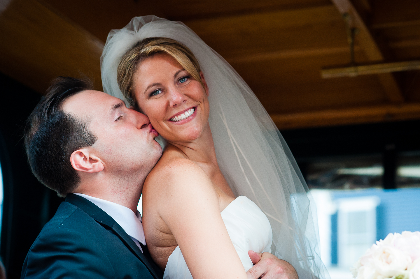 the groom gives his gorgeous bride a kiss on the cheek