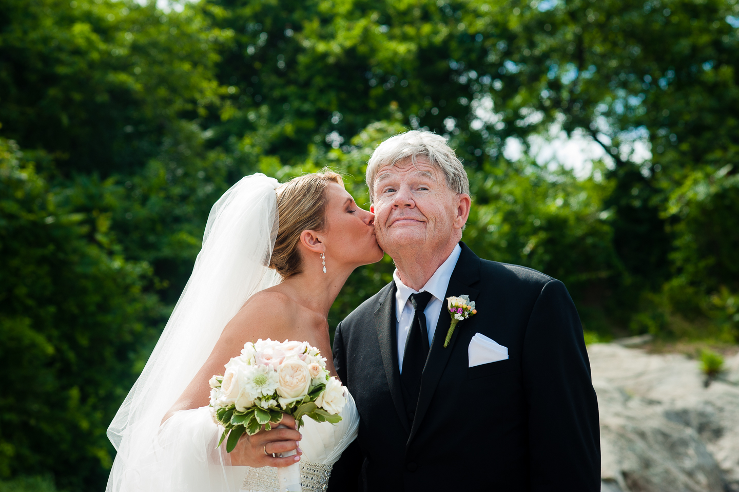 a stunning bride gives her dad a sweet kiss on the cheek during family pictures
