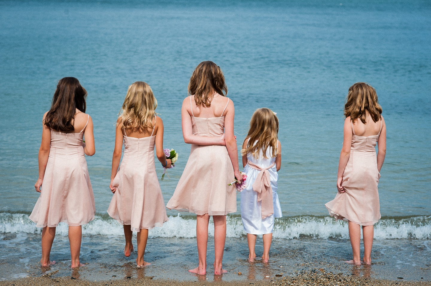 the jr bridesmaids seeing how close they can get to the ocean without getting their dresses wet