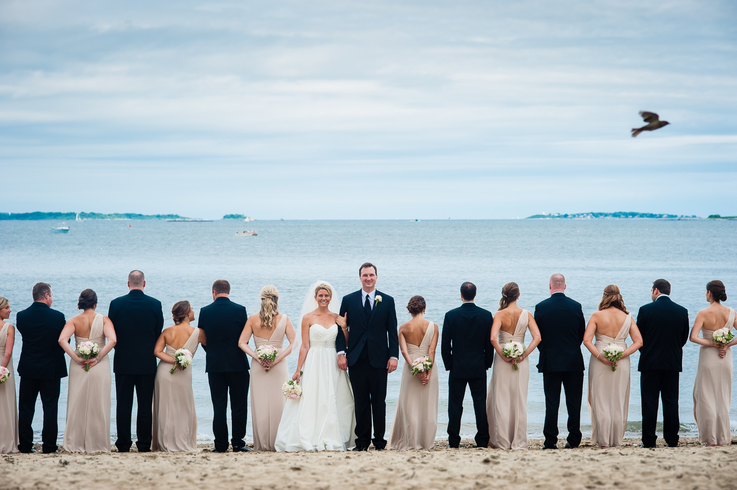 the bride and groom face the camera while the gorgeous wedding party faces the ocean  during this creative wedding party image