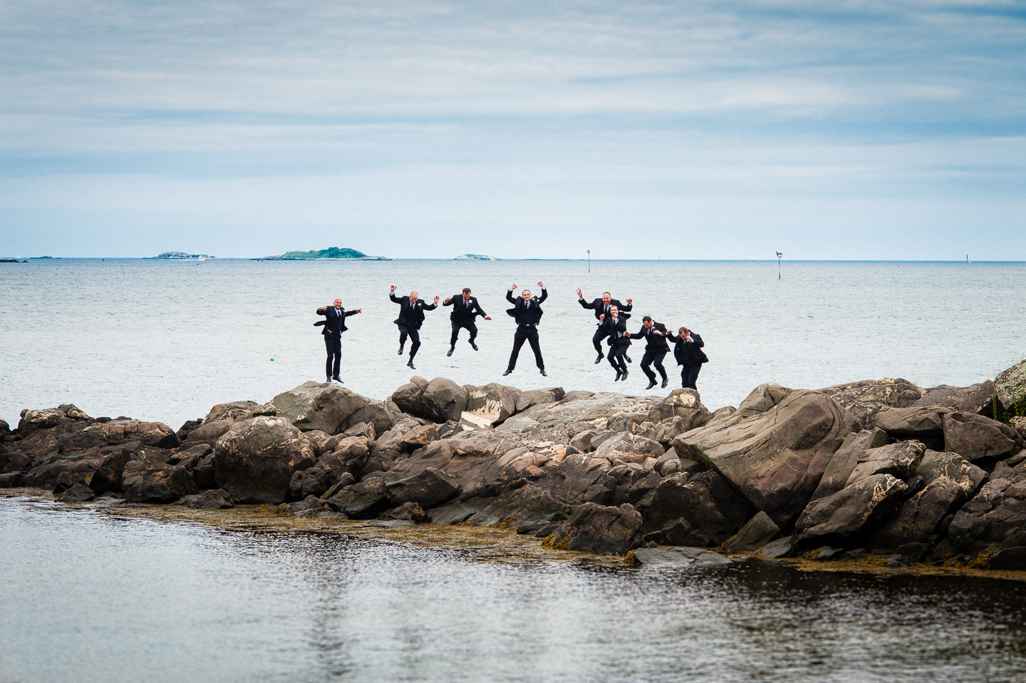 the groom and his groomsmen jumping on some ocean rocks