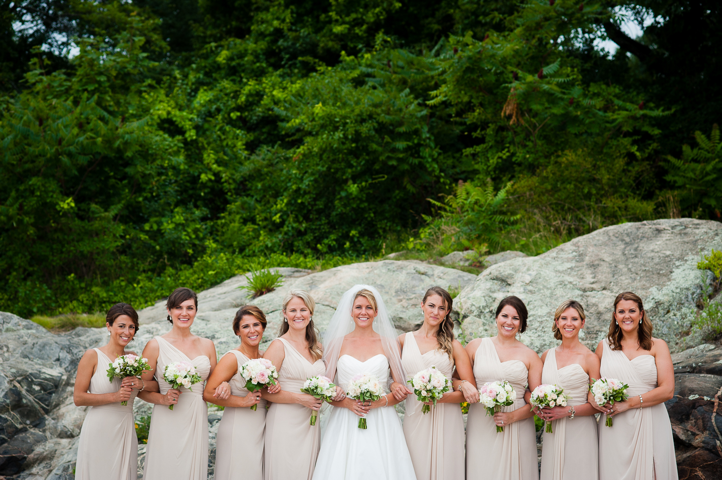 the bride and her gorgeous bridesmaids standing in front of a big rock