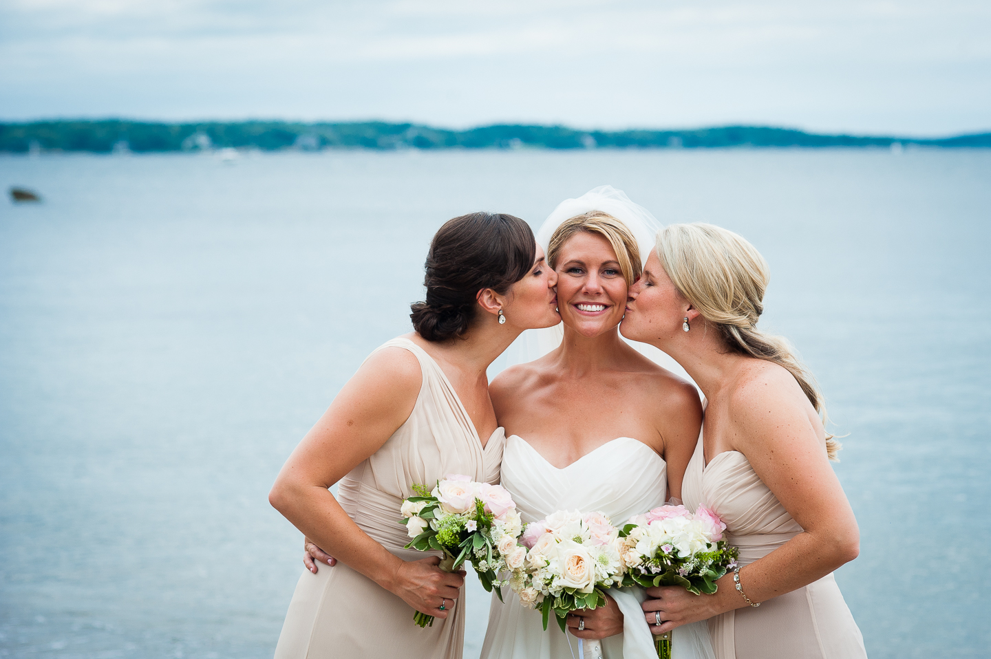 the brides two sisters give her a kiss on the cheek