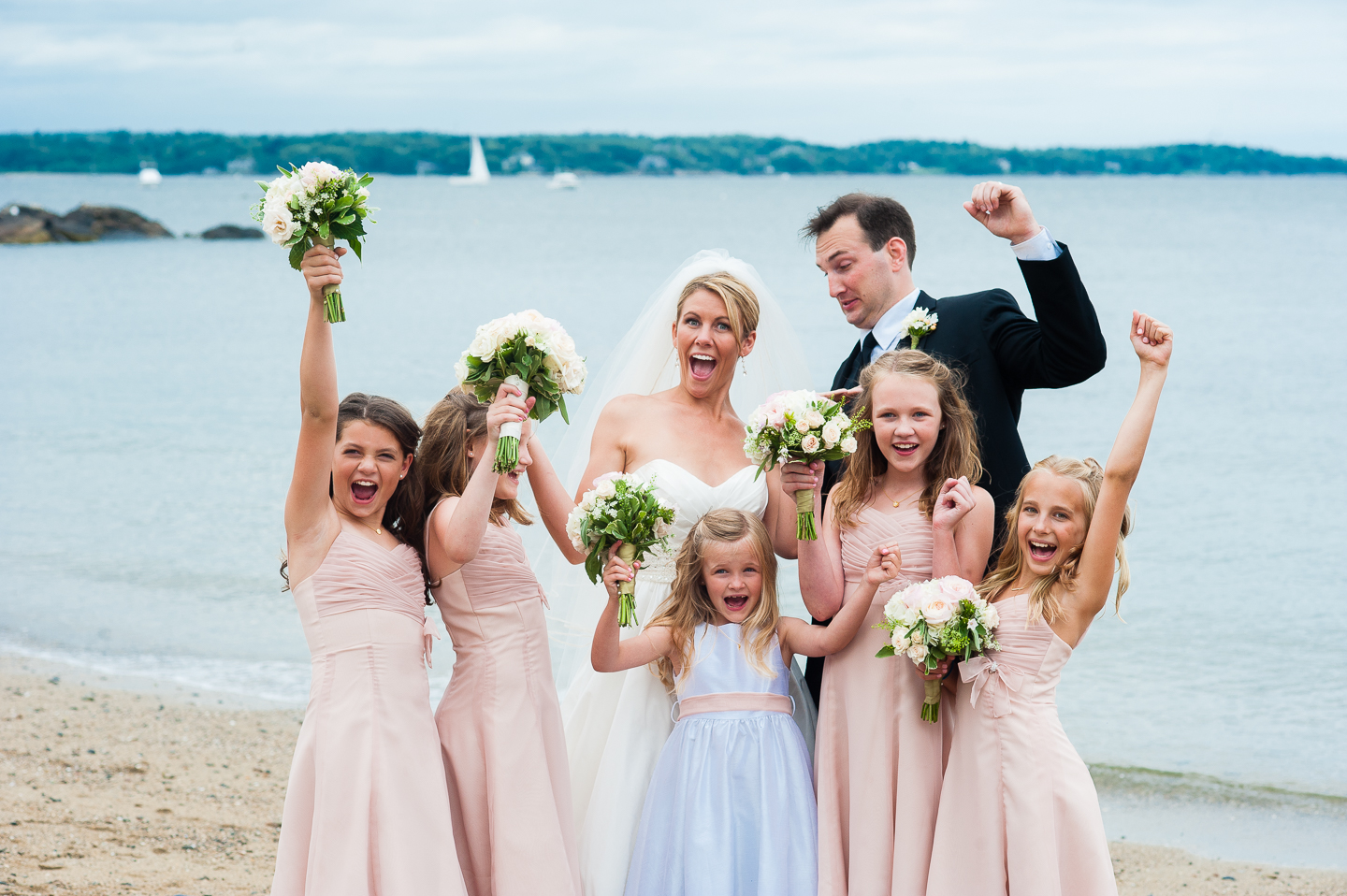 the bride and groom with their adorable jr bridesmaids all cheering