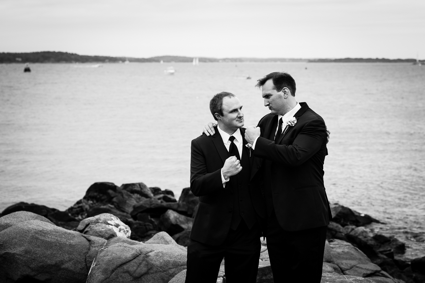 the handsome groom and his brother pose on some rocks by the ocean for a quick picture