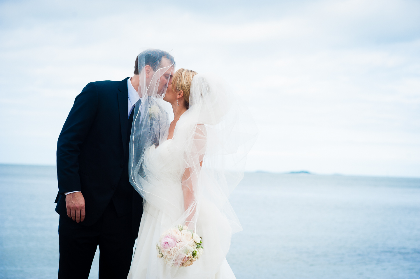 the groom wrapped in brides veil by the ocean