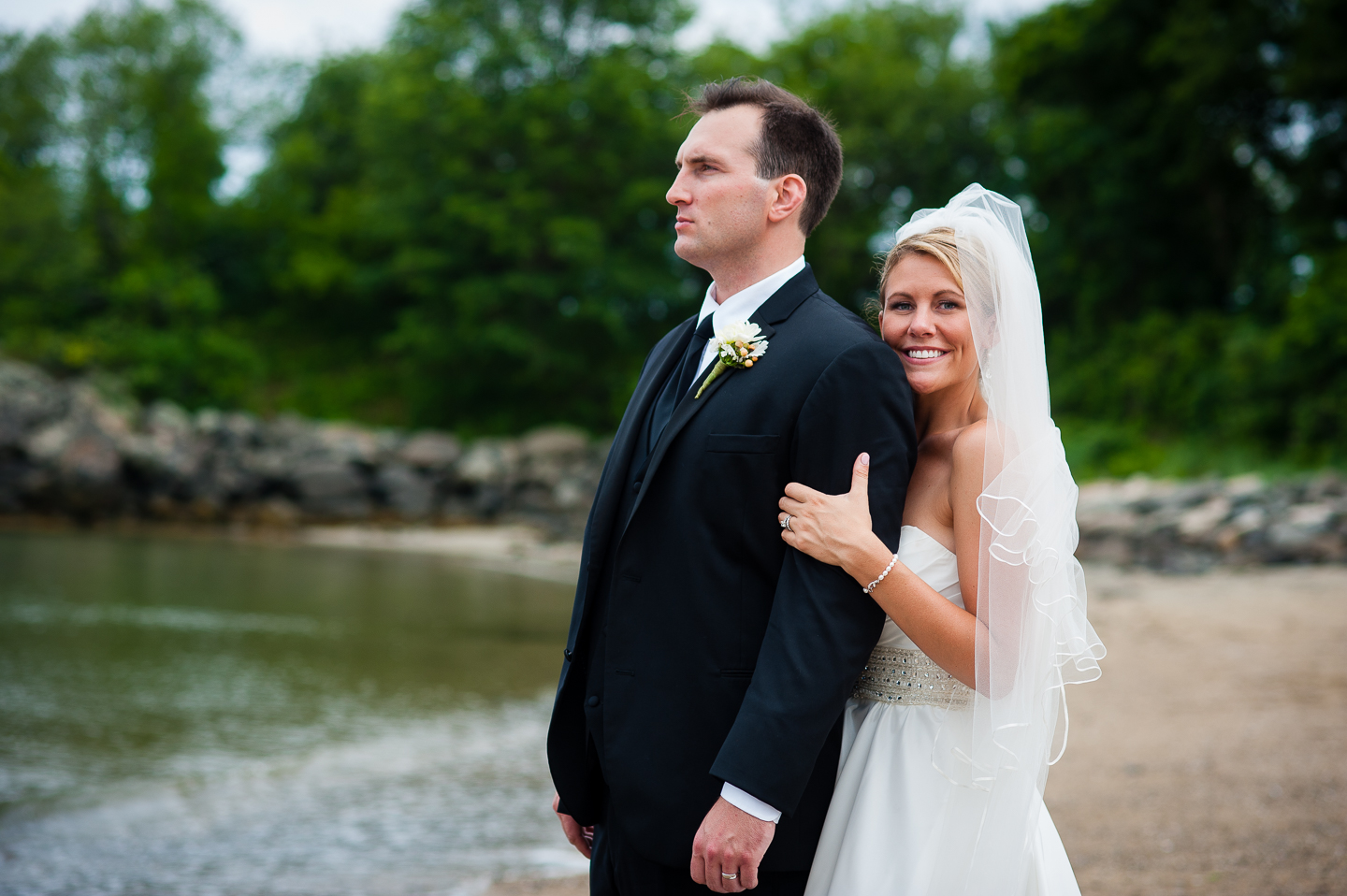 a gorgeous bride rests her cheek on her husbands shoulder during seaside couples portraits