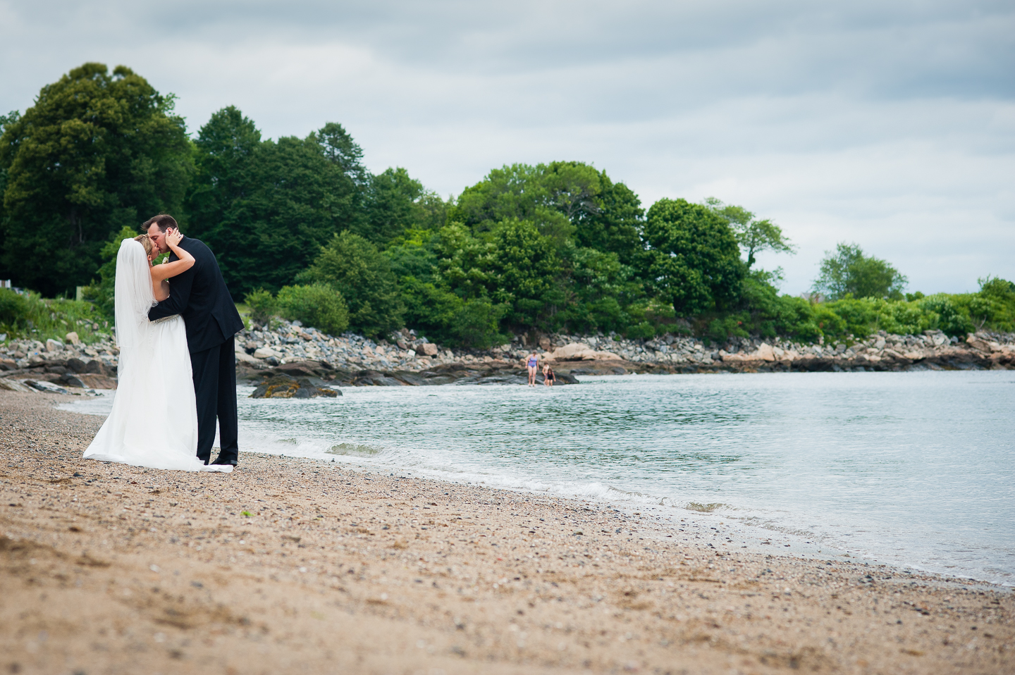 a bride and groom kiss by the ocean  with gorgeous trees behind