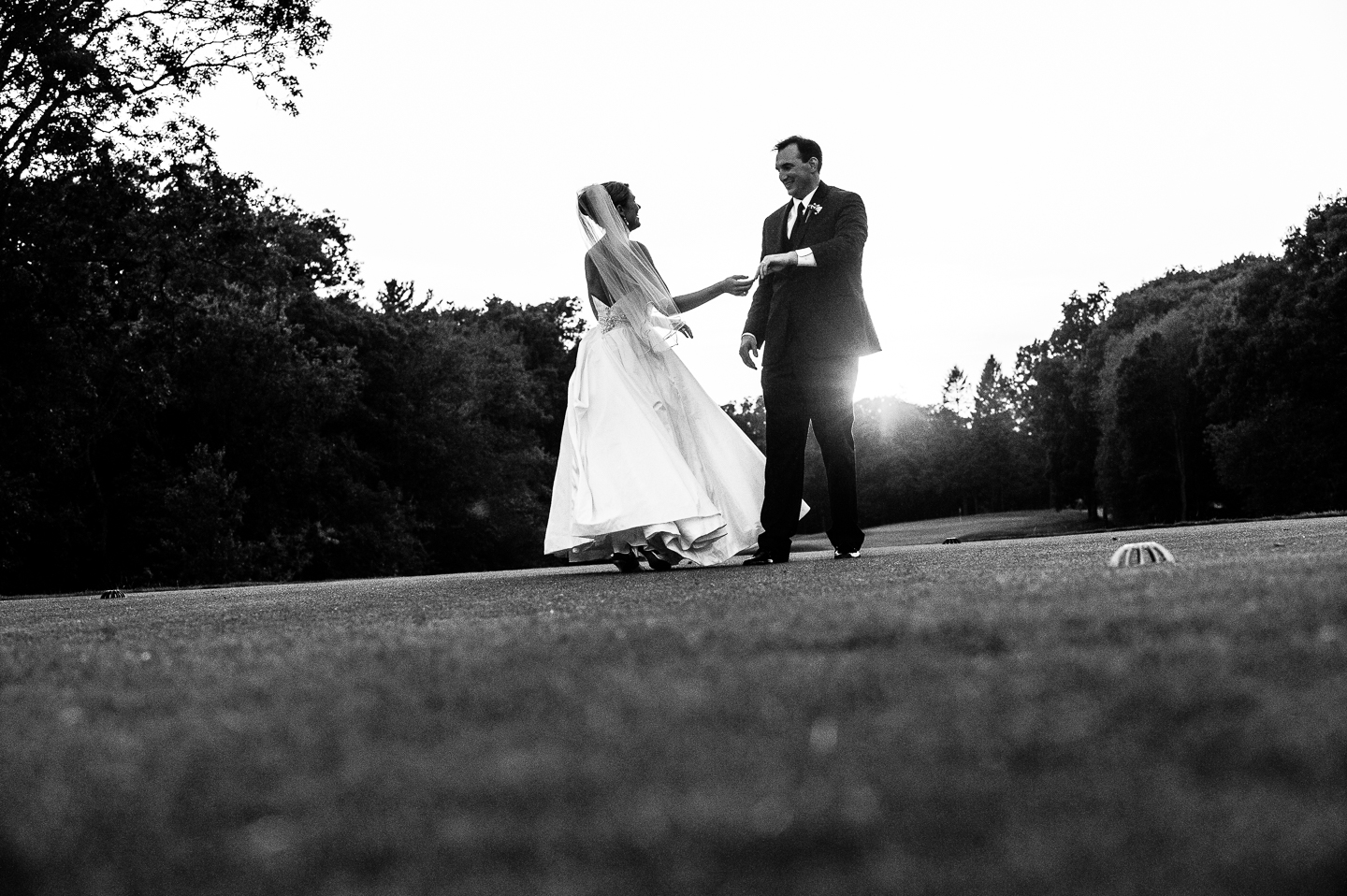 a bride and groom practice their first dance in a field