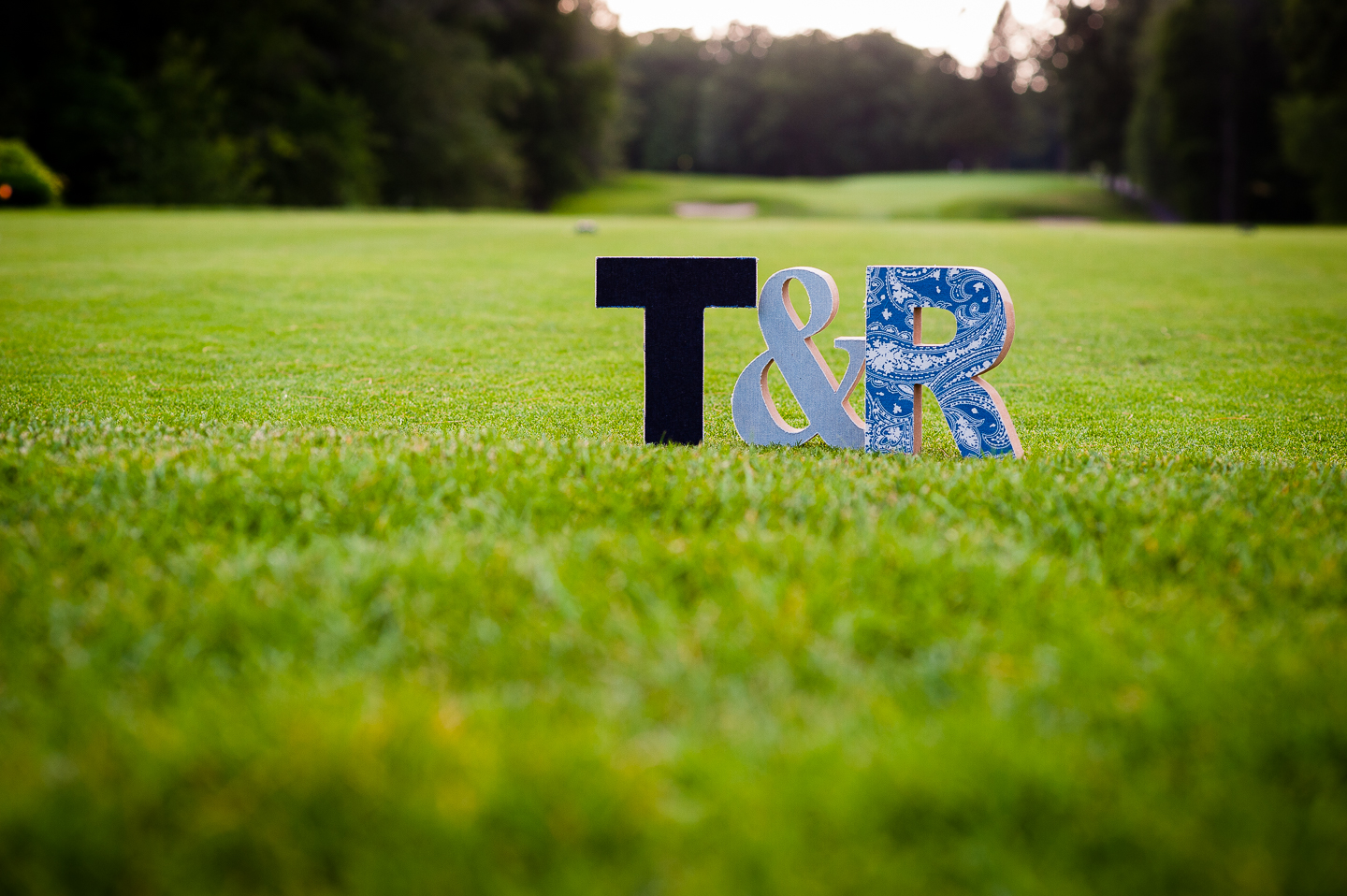 wooden letters cut in the shape of brides and grooms initials are placed on the golf course