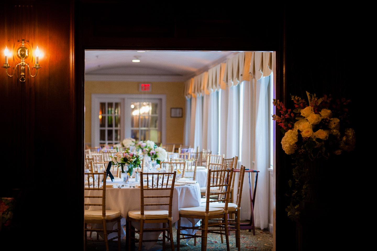 a gorgeous ballroom is decorated by pretty white and pink flowers for this wedding reception