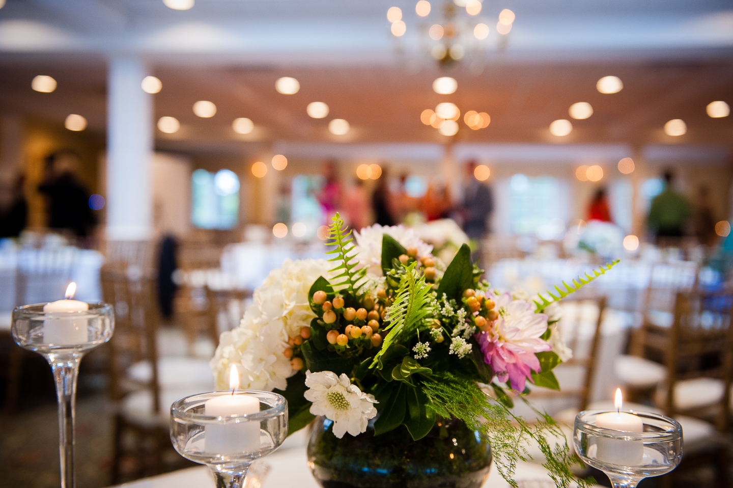 pretty twinkly lights behind one of the floral centerpieces