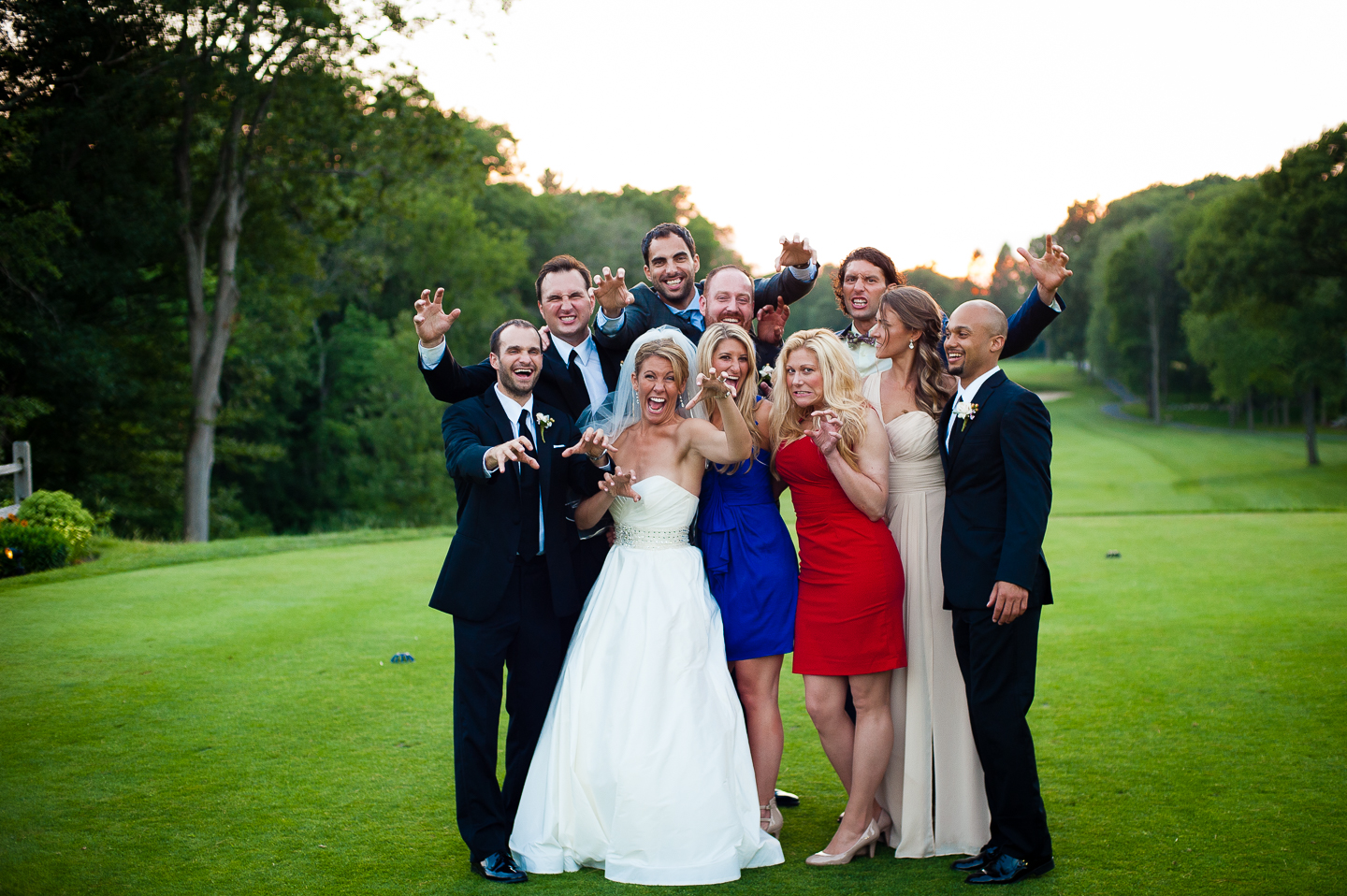 the bride and groom with their friends goofing off on the golf course