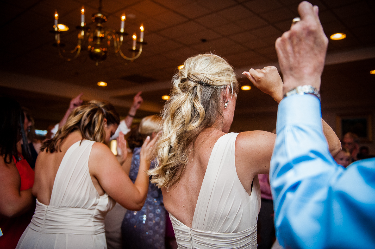 bridemaid surrounded by guests throw their hands in the air