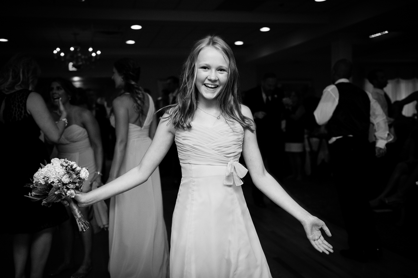 a jr bridesmaid holds the bouquet after catching it