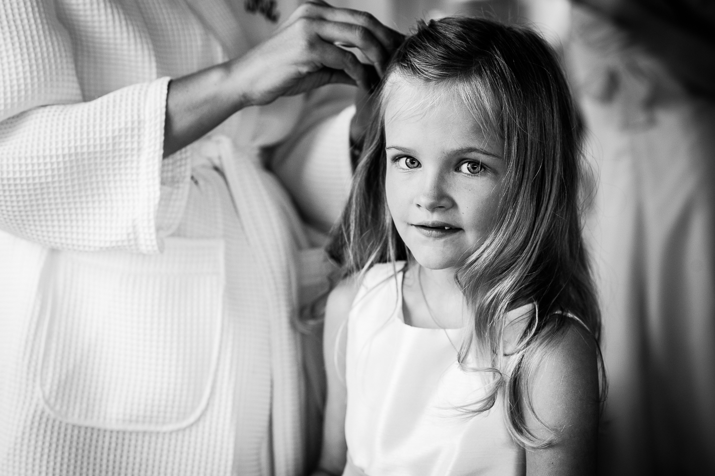cutest flower girl smiles as bride does her hair