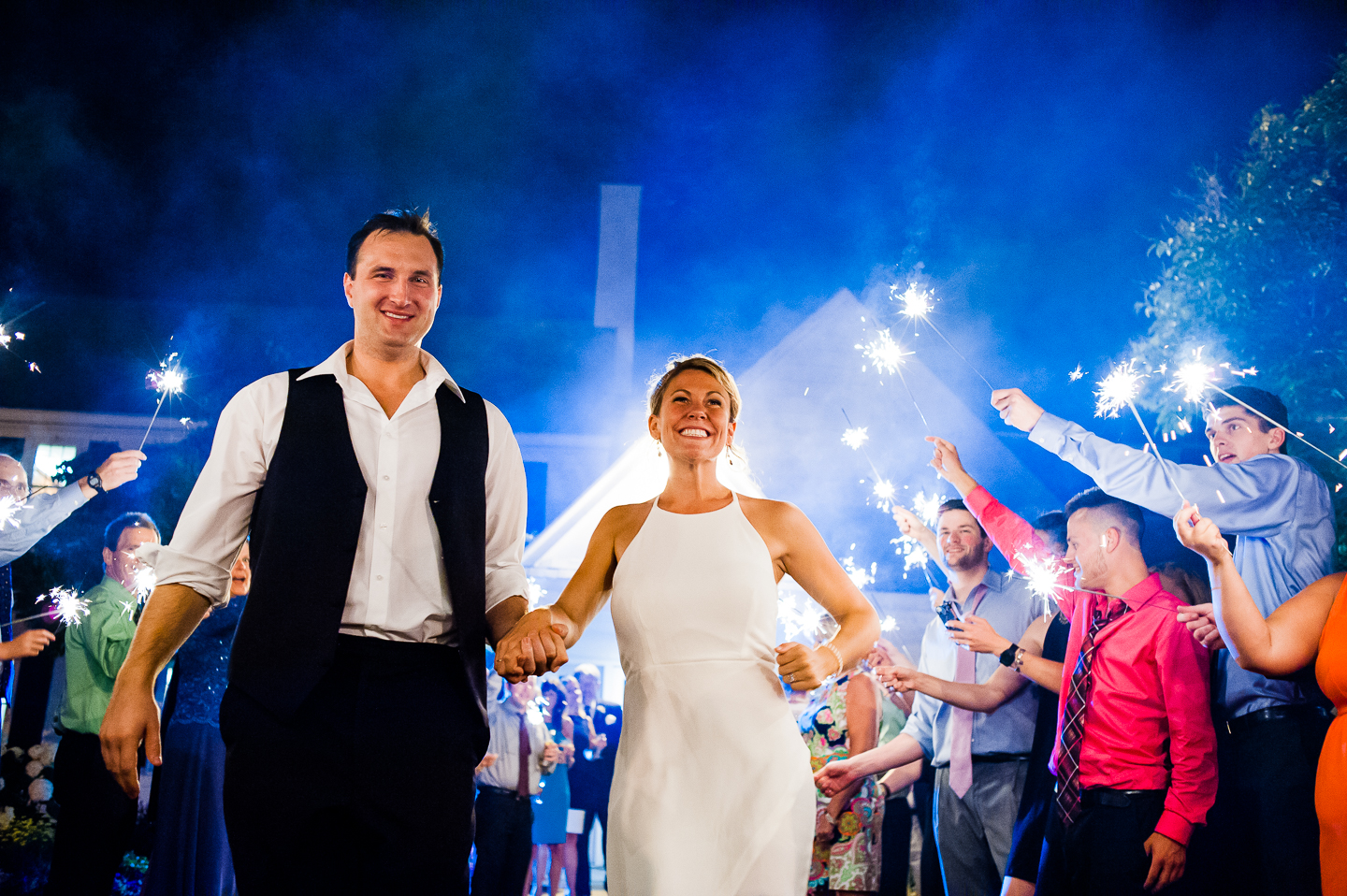 bride and groom happily run down the aisle of sparklers during their send off