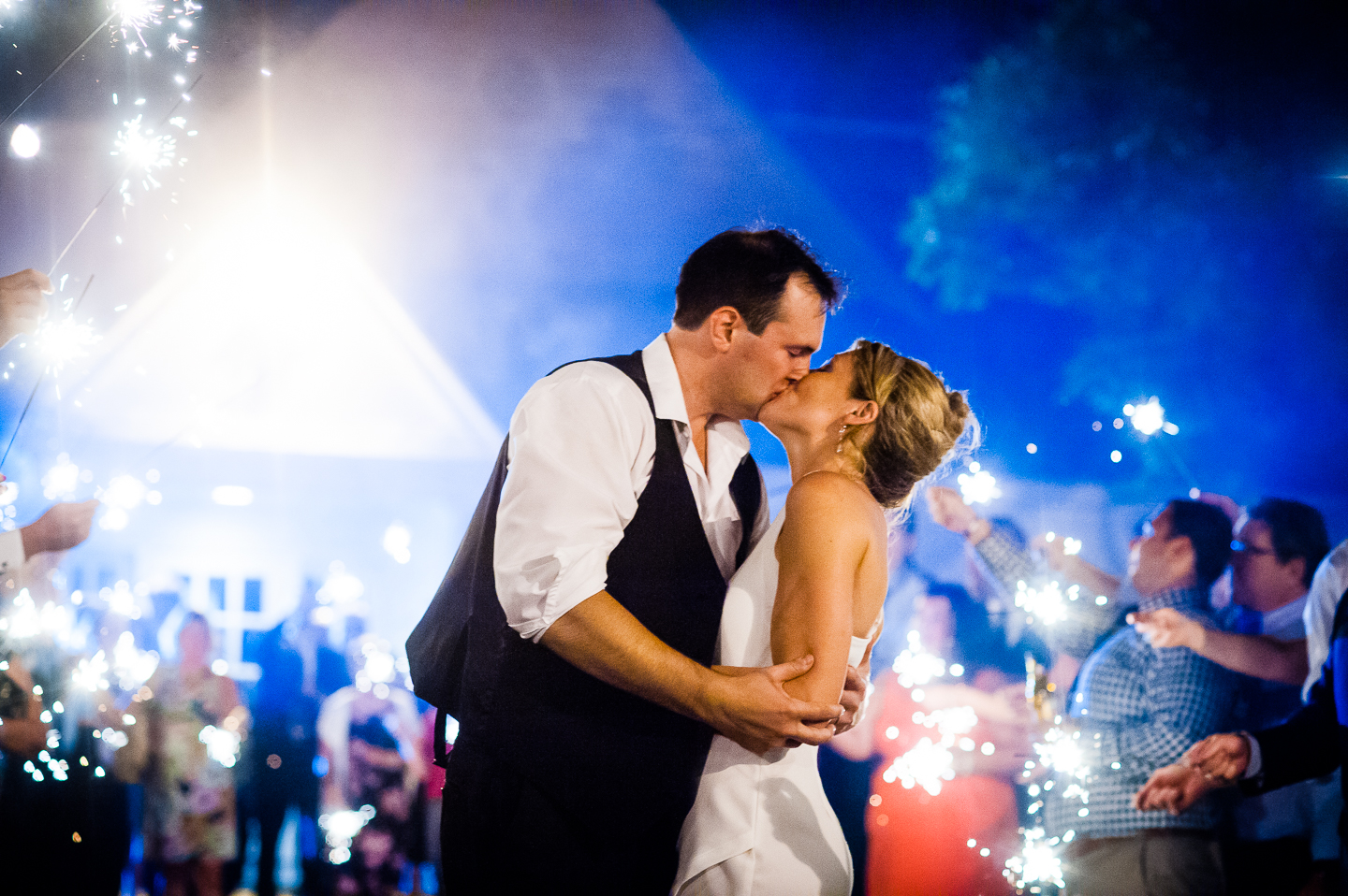 a bride and groom stop to kiss during their sparkler exit at the end of the wedding reception