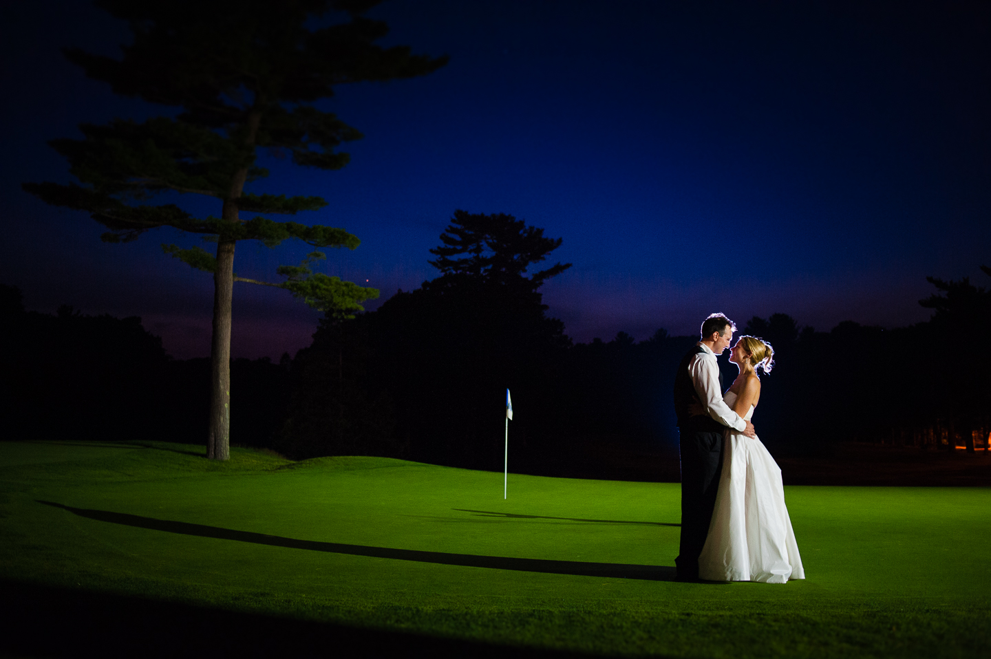 a bride and groom embrace for an end of the night photo on the lit up golf course