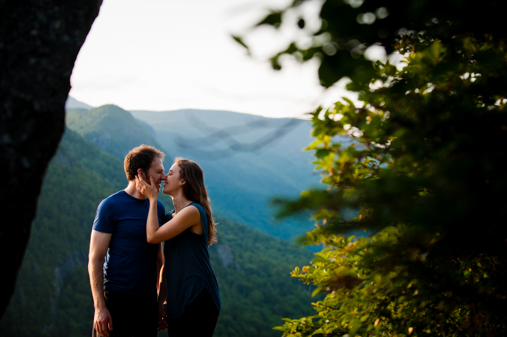 engaged couple kiss with gorgeous mountains behind them