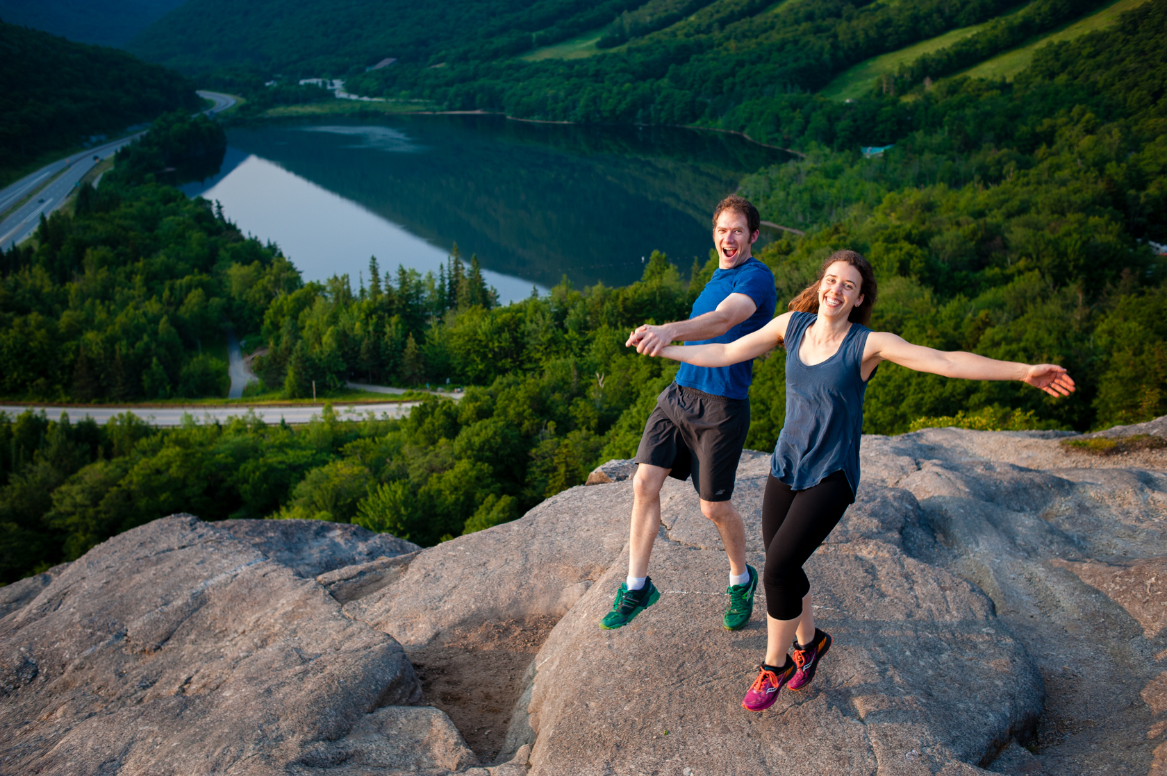 fun couple hold hands and jump during their mountaintop adventure engagement session