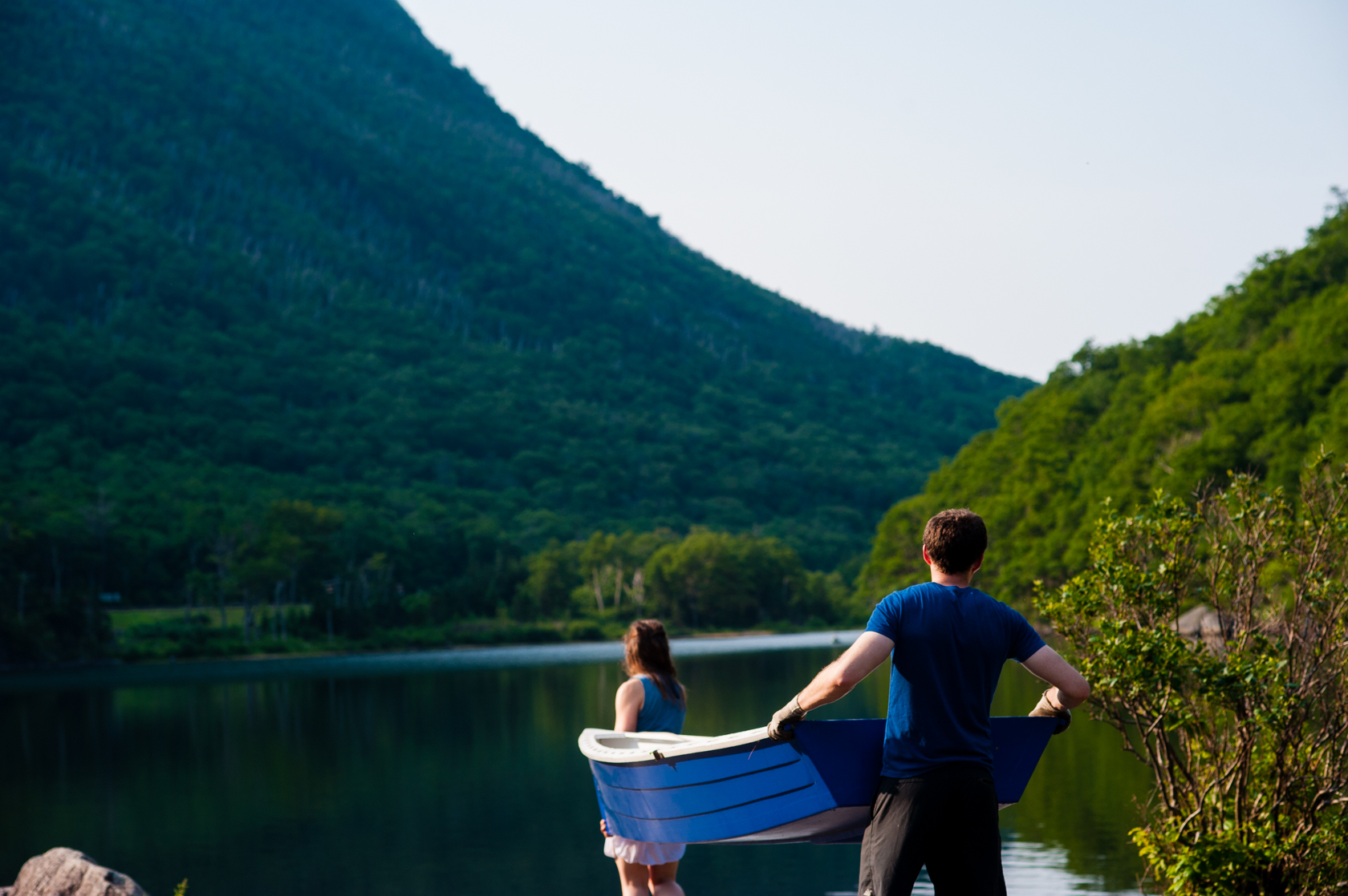young couple carries boat to a beautiful mountain lake