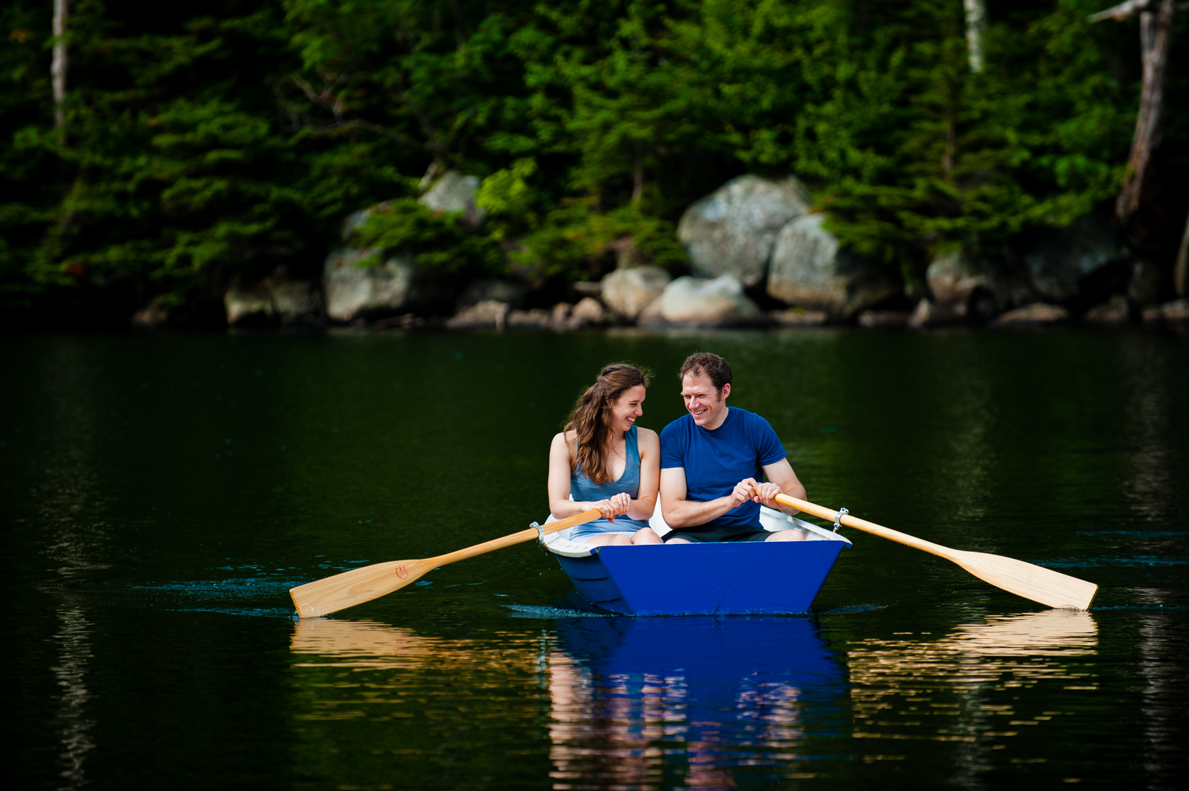 couple laughing as they row their boat on a mountain lake