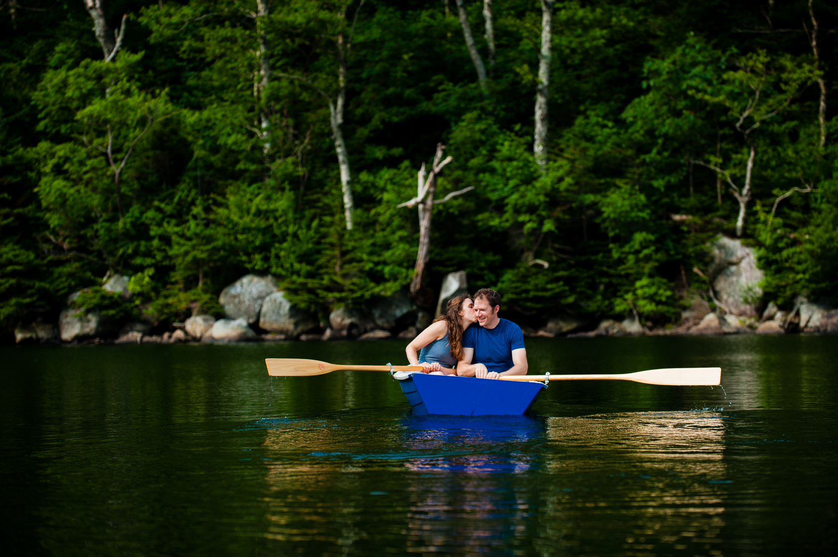 cute couple kisses in a row boat during their mountain lake adventure engagement session