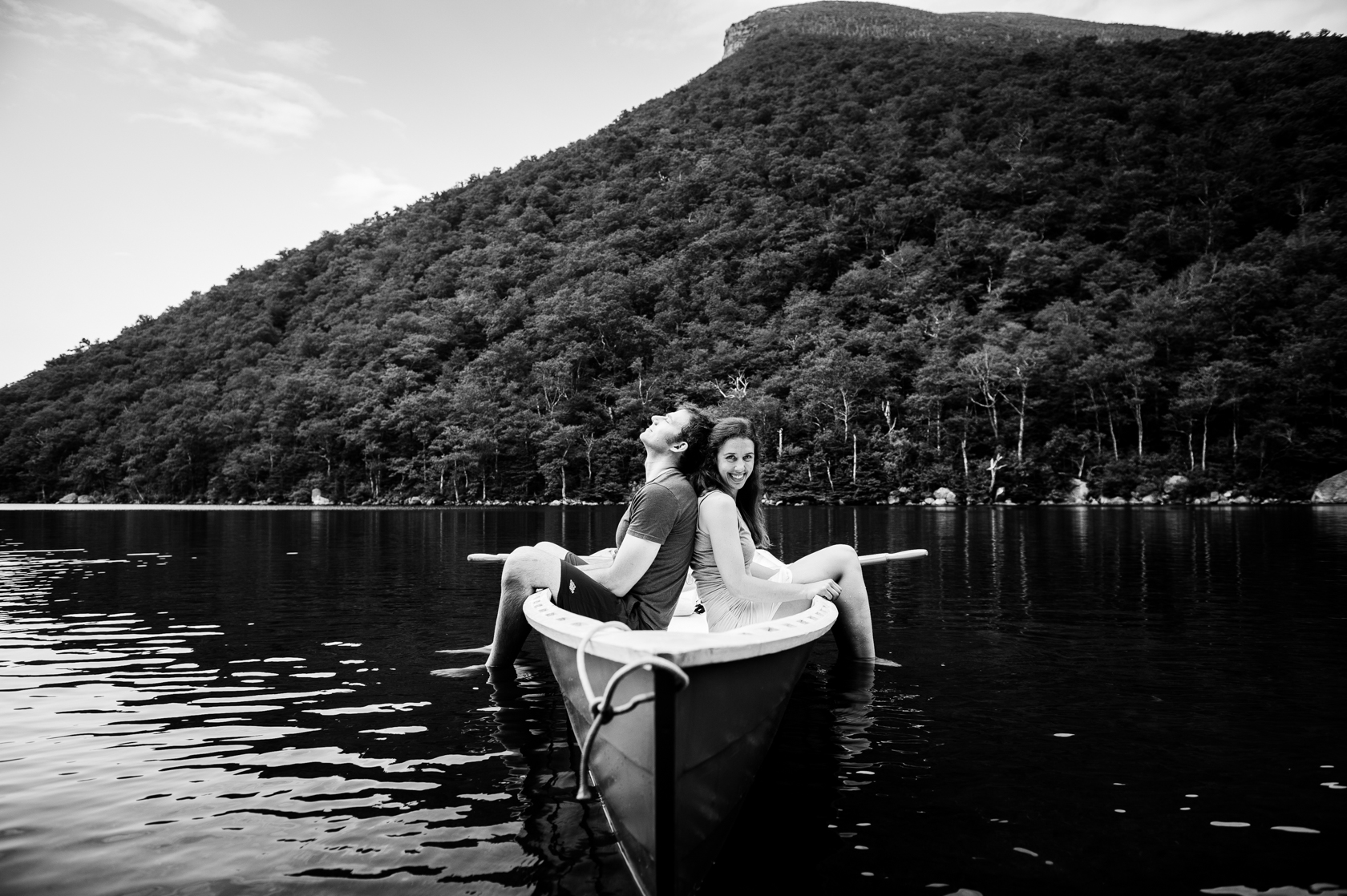 adorable couple sit back to back on their blue row boat