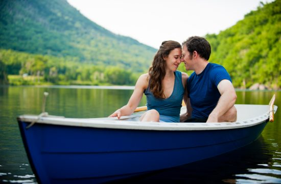 adorable engaged couple embrace during their adventurous engagement session on a lake
