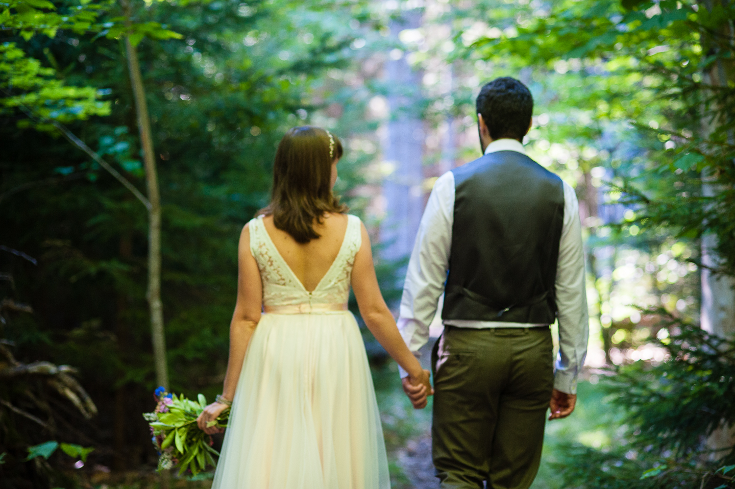 bride and groom hold hands and walk through the forest during their summer mountain wedding